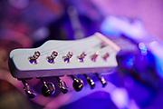 Kop met snaren van een elektrische gitaar. | Headstock with strings from an electric guitar