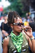 A woman enjoying her Cohiba cigar at the Notting Hill Carnival, London.