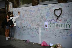 © Licensed to London News Pictures. 15/06/2017. London, UK. Two young women sign a wall of condolence at The scene the day after the a huge fire at a Grenfell tower block in west London. The blaze engulfed the 27-storey building with hundreds of firefighters attending the scene. Photo credit: Ben Cawthra/LNP