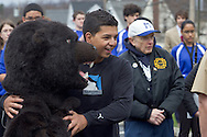 Middletown, New York - A teenager poses for a photograph with the Middie Bear, Middletown High School's mascot, before the start of the 60th annual Middletown Little League parade on April 14, 2013.