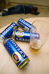 Cans of lager on the table with beaten woman lying on the floor,