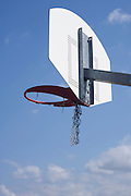 basketball hoop against a blue sky with broken net