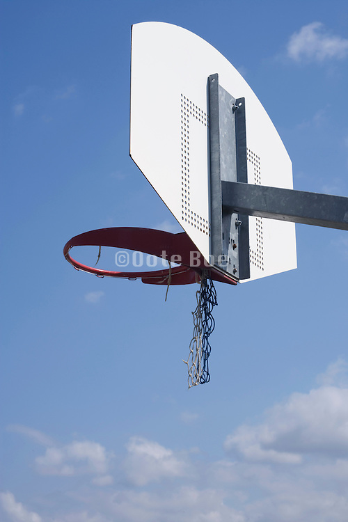 basketball hoop against a blue sky with broken net