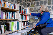 A woman browses books at a community library in a seafront shelter at Borth-y-gest, on 7th October 2021, in Portmadoc, Gwynedd, Wales.