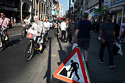 Busy scene on Oxford Street as people cycle past a men at work sign in London, England, United Kingdom.