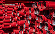 Red plastic sewerage pipes.  The material used here is the thermoplastic polymer polyvinyl chloride (PVC). One of the most commonly produced plastics in the world, PVC is used in a wide variety of products. It can be used with or without varying amounts of plasticiser that make it more flexible or rigid as required.