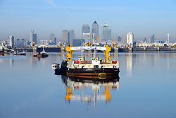 © Licensed to London news pictures. 06/10/2013. A ferry boat reflected in the river in clear blue sky over The Thames Barrier which is having its annual closure. The maintenance closure of the capital's flood defence system is being conducted by the Environment Agency. Spectators gathered to watch the iconic structure, known as the 8th wonder of the world close on a gloriously sunny Autum day. Credit : Mike King/LNP