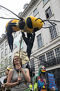 An Extinction Rebellion climate activist holds a large bee puppet during a colourful March for Nature on the final day of their two-week Impossible Rebellion on 4th September 2021 in London, United Kingdom. Extinction Rebellion are calling on the UK government to cease all new fossil fuel investment with immediate effect.