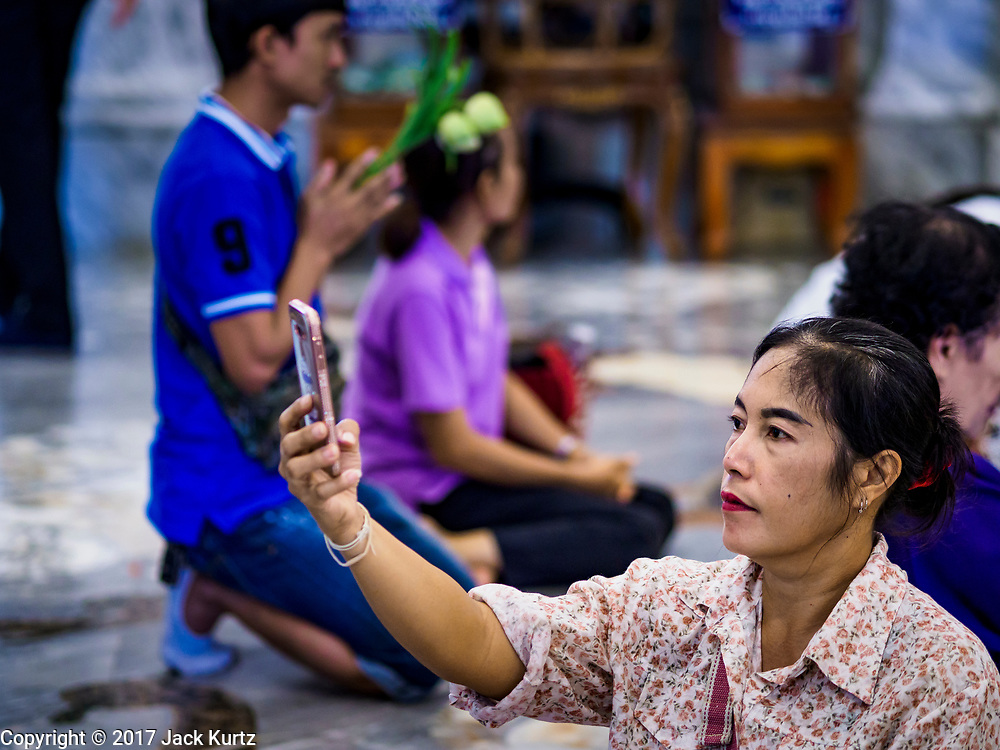 """31 MAY 2017 - CHACHOENGSAO, THAILAND:  A woman takes a selfie with her smart phone in the """"viharn"""" (prayer hall) at Wat Sothon (also spelled Sothorn) in Chachoengsao, Thailand. The temple is one of the largest and most visited in Thailand. People make merit by paying to wrap the Buddha statues in yellow robes. The temple is most famous because people leave hard boiled eggs as an offering at the temple. They ask for business success or children and leave hundreds of hard boiled eggs.     PHOTO BY JACK KURTZ"""