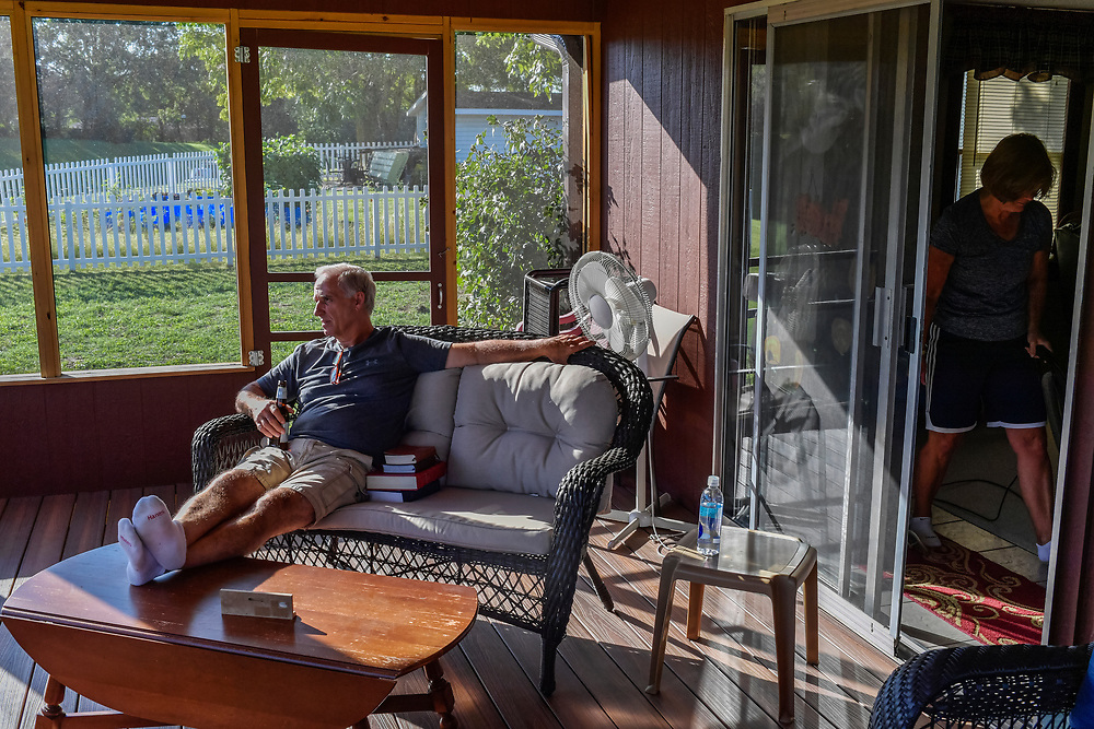 """Snoddy's co-owner Jim Snoddy drinks a beer on his back porch as his wife Sherry cleans the living room of their home in Boonville on Thursday, September 26, 2019. Sherry works as a housecleaner around the area. The Snoddy's routinely pass their afternoons together at home. Through this tough time, Jim has leaned on his wife and his faith, attending church and reading his daily devotions each morning. """"I can't remember the last time I didn't,"""" he says."""