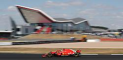 Ferrari's Sebastian Vettel drives past the grandstand during the 2018 British Grand Prix at Silverstone Circuit, Towcester.
