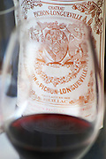 A glass of wine with the label of a bottle seen through the glass - label without vintage (digitally removed) - Chateau Baron Pichon Longueville, Pauillac, Medoc, Bordeaux, Grand Cru