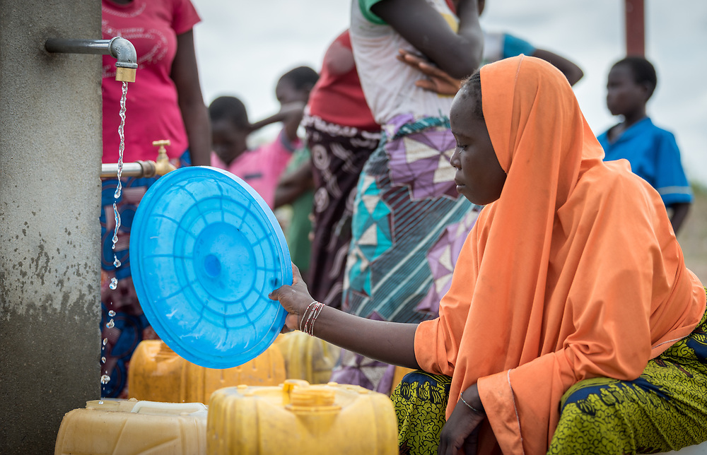 30 May 2019, Mokolo, Cameroon: A young woman waits for her jerry cans to fill up at one of the tapstands in Minawao camp. The Minawao camp for Nigerian refugees, located in the Far North region of Cameroon, hosts some 58,000 refugees from North East Nigeria. The refugees are supported by the Lutheran World Federation, together with a range of partners.