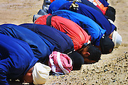 Firefighters from the Kuwait Oil Company (called KWWK: Kuwait Wild Well Killers) pray at noon by the second oil well fire they were working on in Iraq's Rumaila Oil field. The Rumaila field is one of Iraq's biggest oil fields with five billion barrels in reserve. Rumaila is also spelled Rumeilah.