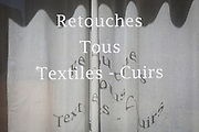 Shadows of French lettering outside a shop offering the retouching of textiles and leather, on 23rd May, 2017, in Narbonne, Languedoc-Rousillon, south of France