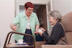 Carer giving elderly woman cup of tea,