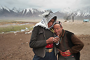 Young Kyrgyz men play with their phone. There is no mobile reception in this remote mountain region, and these are used to look at pictures and listen to music...Qayoom (left) and Kossim..The Kyrgyz settlement of Tchelab, near Chaqmaqtin lake, Haji Bootoo Boi's camp...Trekking through the high altitude plateau of the Little Pamir mountains (average 4200 meters) , where the Afghan Kyrgyz community live all year, on the borders of China, Tajikistan and Pakistan.