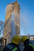 London Fire Brigade, station training session on the second floor of the tower. Firefighters spray water on to the tower.