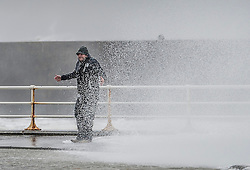 """© London News Pictures. 08/02/2014. Aberystwyth, UK. <br /> 43 year old RUSSEL THOMAS, from Worcester, gets caught by a huge wave as gale force winds strike the sea walls at Aberystwyth, Wales at high tide. The winds are forecast to strengthen throughout the day, gusting up to 70 or 80 mph, and with the rising tide, their impact could be potentially damaging again. An amber """"be prepared"""" warning  has been issued by the Met Office for wind,. Photo credit: Keith Morris/LNP"""