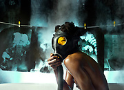 Gas Masked black woman seems to be in a bath tub showing X-Rays hanging behind her.