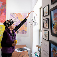 Be Sargent holds up a sculpture as she prepares to hang it in the window at OPO on Second St. in Gallup Wednesday, Oct. 10, 2018 before arts crawl this weekend.