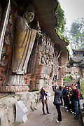 Tourists at Dazu rock carvings of Buddha of Mercy at Mount Baoding, Chongqing, China