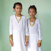 Portrait of two Muslim Cham girls wearing white dresses and bronze and copper jewellery at their Karoh (maturity) ceremony in Van Lam, Ninh Thuan province, Central Vietnam. Cham girls usually in groups of around 5, undergo a Karoh (maturity) ceremony, one of the most important ritual events of their lives and if it has not taken place, the girl cannot marry. The Cham, a Muslim community of around 39,000 people living along the coast of Central Vietnam are one of the 54 ethnic groups recognised by the Vietnamese government.