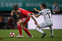 """Gareth Bale, left, of Wales national football team kicks the ball to make a pass against Diego Laxalt of Uruguay national football team in their final match during the 2018 Gree China Cup International Football Championship in Nanning city, south China's Guangxi Zhuang Autonomous Region, 26 March 2018.<br /> <br /> Edinson Cavani's goal in the second half helped Uruguay beat Wales to claim the title of the second edition of China Cup International Football Championship here on Monday (26 March 2018). """"It was a tough match. I'm very satisfied with the result and I think that we can even get better if we didn't suffer from jet lag or injuries. I think the result was very satisfactory,"""" said Uruguay coach Oscar Tabarez. Wales were buoyed by a 6-0 victory over China while Uruguay were fresh from a 2-0 win over the Czech Republic. Uruguay almost took a dream start just 3 minutes into the game as Luis Suarez's shot on Nahitan Nandez cross smacked the upright. Uruguay were dealt a blow on 8 minutes when Jose Gimenez was injured in a challenge and was replaced by Sebastian Coates. Inter Milan's midfielder Matias Vecino of Uruguay also fired at the edge of box from a looped pass but only saw his attempt whistle past the post. Suarez squandered a golden opportunity on 32 minutes when Ashley Williams's wayward backpass sent him clear, but the Barca hitman rattled the woodwork again with goalkeeper Wayne Hennessey well beaten."""