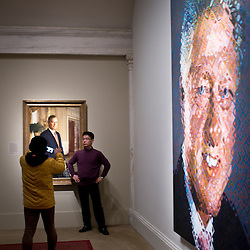 A Chinese tourist poses in front of a portrait of President George W. Bush next to a Chuck Close portrait of President Bill Clinton inside the American Presidents' exhibit in the National Portrait Gallery of the Smithsonian Institution in the Chinatown neighborhood of Washington, DC.