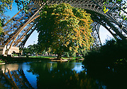 Eiffel Tower and park with blue skyand pond underneath.