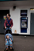 Father with a tired baby pushes his child in a pram away from a cashpoint ATM machine.