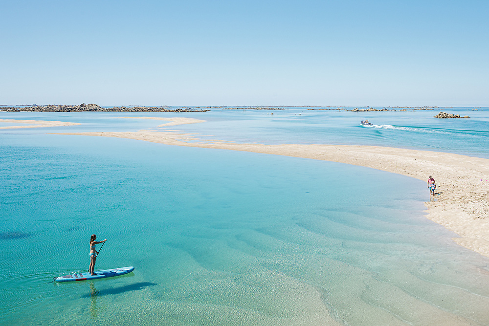 Paddleboarding through the glassy calm and clear water towards a priavte quiet sandbank at the partadise beach location, the Minquiers off the coast of Jersey CI