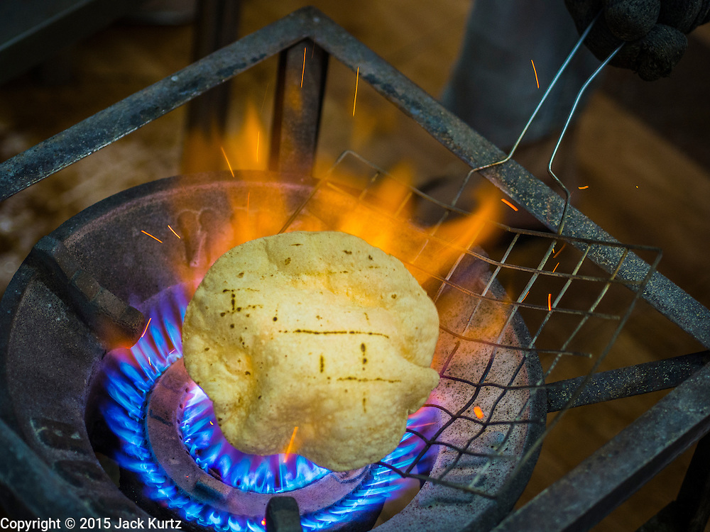 """08 FEBRUARY 2015  BANGKOK, THAILAND: Chapatis (unleavened Indian flatbread) are toasted over an open flame in the kitchen before the communal meal at the Gurdwara Siri Guru Singh Sabha in Bangkok. Thailand has a small but influential Sikh community. Sikhs started coming to Thailand, then Siam, in the 1890s. There are now several thousand Thai-Indian Sikh families. The Sikh temple in Bangkok, Gurdwara Siri Guru Singh Sabha, was established in 1913. The current building, adjacent to the original Gurdwara (""""Gateway to the Guru""""), was built in 1979. The Sikh community serves a daily free vegetarian meal at the Gurdwara that is available to people of any faith and background.    PHOTO BY JACK KURTZ"""