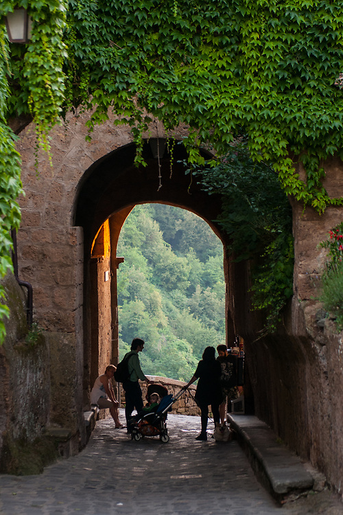 """Citizen rest under a portico in the village of Civita di Bagnoregio.<br /> Civita di Bagnoregio is a town in the Province of Viterbo in central Italy, a suburb of the comune of Bagnoregio, 1 kilometre (0.6 mi) east from it. It is about 120 kilometres (75 mi) north of Rome. Civita was founded by Etruscans more than 2,500 years ago. Bagnoregio continues as a small but prosperous town, while Civita became known in Italian as La città che muore (""""The Dying Town""""). Civita has only recently been experiencing a tourist revival. The population today varies from about 7 people in winter to more than 100 in summer.The town was placed on the World Monuments Fund's 2006 Watch List of the 100 Most Endangered Sites, because of threats it faces from erosion and unregulated tourism."""