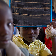 A Koumbadiouma primary school student shows off her mastery of the letter 'L'. Kolda, Senegal.