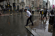 Storm Georgina swept across parts of Britain and in central London, lunchtime office workers were caught out by torrential rain and high winds, on 24th January 2018, in London, England. Pedestrians resorted to leaping across deep puddles at the junction of New Oxford Street and Kingsway at Holborn, the result of overflowing drains. Second in a sequence of five photos.