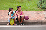 Two young girls wait for the parade to come down the street.