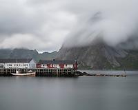 Red Rorbu cabins and Olstind mountain peak swept by clouds, Hamnøy, Moskenesøy, Lofoten Islands, Norway