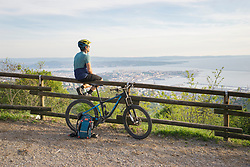 Mountain biker sitting on wooden railing and looking at sea and city
