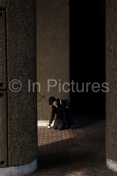 A man kneeling down while using a mobile phone at the Barbican Centre on the 12th September in London in the United Kingdom.