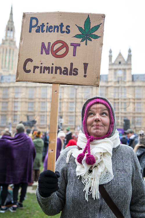 © Licensed to London News Pictures. 23/02/2018. London, UK. A woman holds a sign calling for the legalisation of cannabis for medicinal use at a protest opposite Parliament while MPs debate the issue in The House of Commons. Photo credit: Rob Pinney/LNP