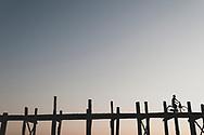 Amarapura, Myanmar - November 9, 2011: At sunset, a Burmese man rides his bicycle across the U Bein Bridge in Amarapura, on the outskirts of Mandalay. This bridge was built around 1850 and, at 1.2 kilometers, is one of the longest teakwood bridges in the world.