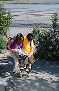 Alaska, Seward. Two children look at a map to find the best way to Exit Glacier.