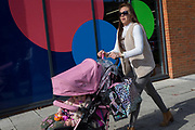 A mother pushes her childs buggy past the circles of a local gym, on 2nd October 2019, in Sutton, London, England.  Voters in Sutton voted 53.7% in favour of Brexit during the 2016 referendum.