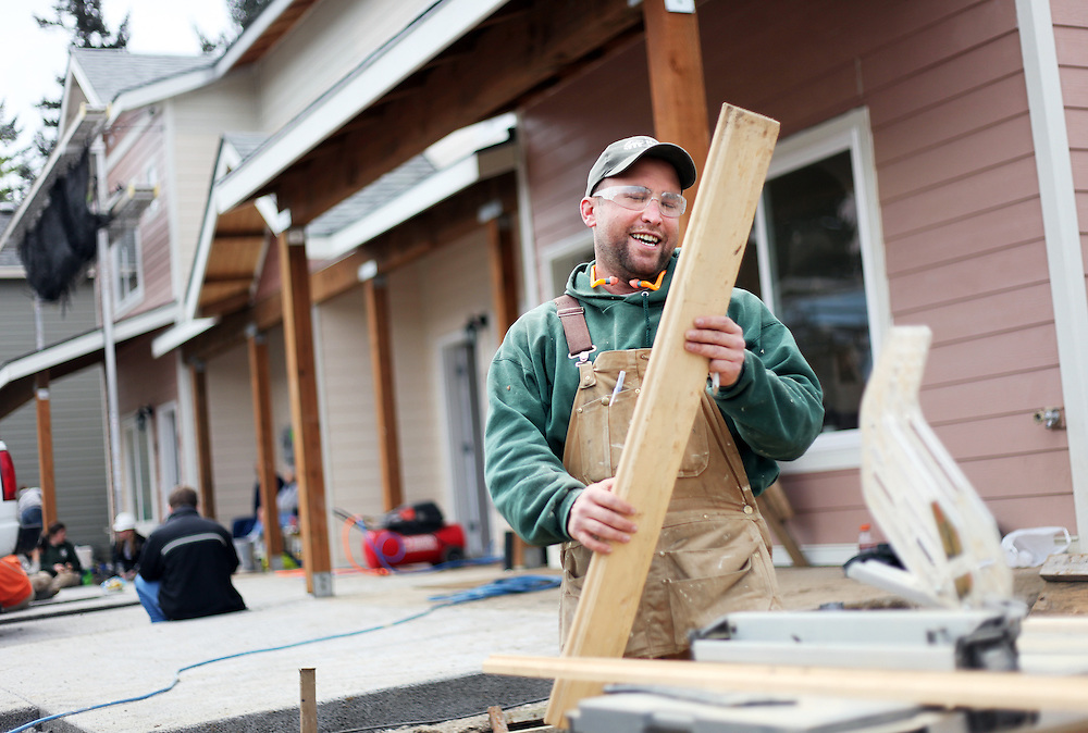 Justin Collinson saws walnut wood for a gate on a Habitat for Humanity work site...John Gray was born 92 years ago and grew up poor in rural Oregon. He made a fortune in the chainsaw industry after World War II, and now he has donated more than a million dollars to Habitat for Humanity to buy land in Portland for low-income housing. Volunteers work to build solid foundations on the largest of these land parcels on Wednesday, May 2, 2012.