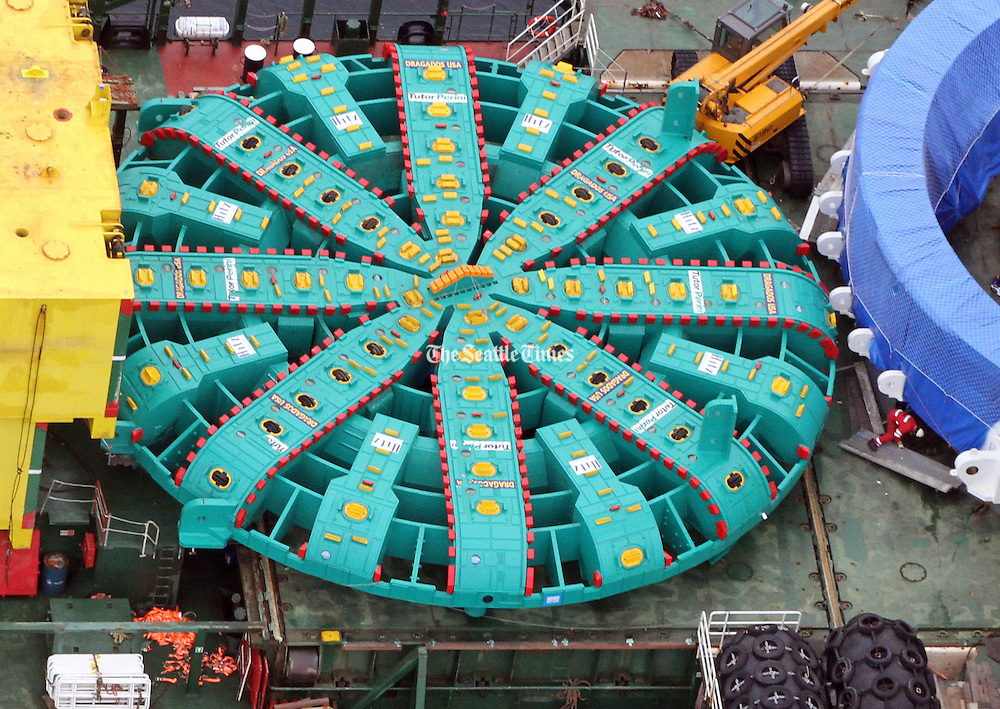 A crew member of the ship carrying Bertha, the giant boring machine, is in red (far right) dwarfed by the 57 1/2-foot cutting face of the machine. <br /> Alan Berner / The Seattle Times