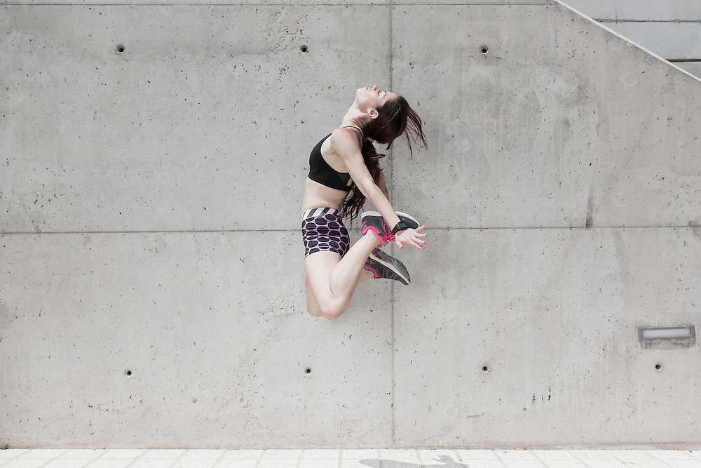 Young woman jumping against concrete wall