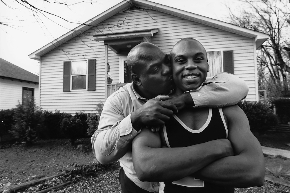 Emmanuel Williams with his father, Johnny, in front of the Habitat House that he watched his parents build.