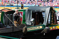 Little Venice, London, April 30th 2017. Narrowboaters from all over the uK gather for the annual Canalway Cavalcade, held on the May Day Bank holiday weekend, organised by the Inland Waterways Association, where boaters get the chance to display their immaculately prepared and brightly painted craft as well as compete in various manoeuvring tests. PICTURED: A man throws a mooring rope from the bow of his narrowboat.<br /> Credit: ©Paul Davey<br /> To licence contact: <br /> Mobile: +44 (0) 7966 016 296<br /> Email: paul@pauldaveycreative.co.uk<br /> Twitter: @pauldaveycreate