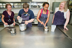 Students with learning disabilities learning to cook in lesson at special school,